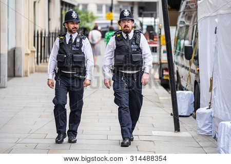 London, Uk, July, 2019. Two British Police Officers Patrolling The Streets Of England Wearing Stab V