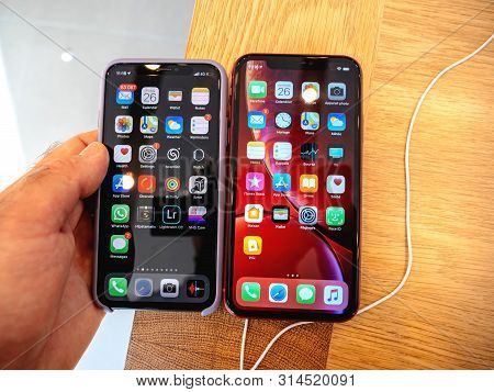 Paris, France - Oct 26, 2018: Man Hand Holding Latest Red Iphone Xr Smartphone And Old Iphone Xs Dur