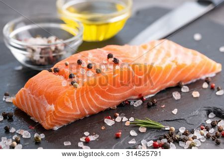 Raw salmon fillet with pepper, salt and rosemary on a stone board. Cooking red fish, salmon. The concept of healthy eating.