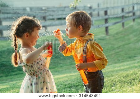 Funny Caucasian Children Girl And Boy Blowing Soap Bubbles In Park At Summer Sunset. Real Authentic