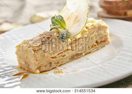 Restaurant Confectionery Course with Napoleon Dessert or Mille-Feuilles on Rustic Tablecloth Background. Exquisite Serving Rectangular Piece of Millefeuille, Filo or Tompouce Puff Pastry