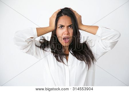 Stressed worried woman shocked with unexpected news. Frowning beautiful young Latin woman in white shirt holding head and gasping. Surprise or shock concept poster