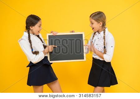 Learning fun at lesson. Cute small schoolchildren reciting lesson at blackboard on yellow background. Little schoolgirls having lesson in primary school. Most interesting lesson ever. poster
