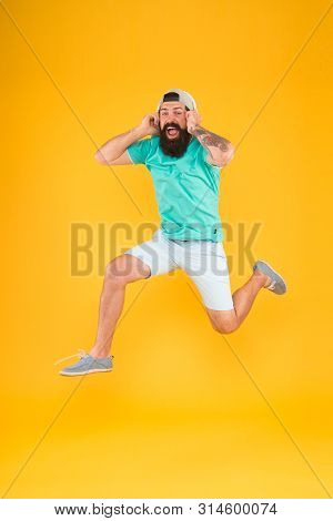 Happy Music. Happy Hipster Jumping On Music On Yellow Background. Bearded Man Enjoying Song Playing