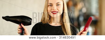 Young Hairstylist Holding Blow Dryer And Hairbrush. Blonde Hairdresser Showing Hairdryer And Red Com