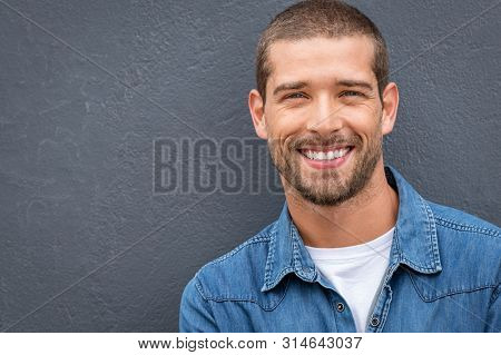 Closeup portrait of a happy young man smiling on gray background. Handsome casual guy with beard looking at camera. Portrait of a cheerful stylish man isolated against gray wall with copy space.