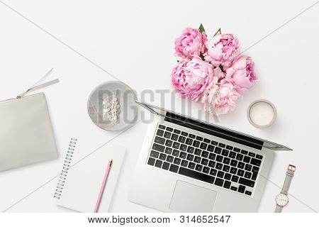 bright feminine workspace with open laptop computer, office supplies, fresh flowers, stylish clutch bag and other accessories on a white desk, top view / flat lay, copyspace for your text