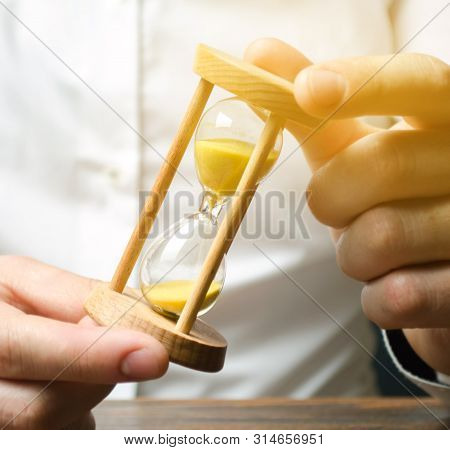 Businessman Holds Clock In Hands. Concept Of Saving Time And Money. Time Management. Planning Work.