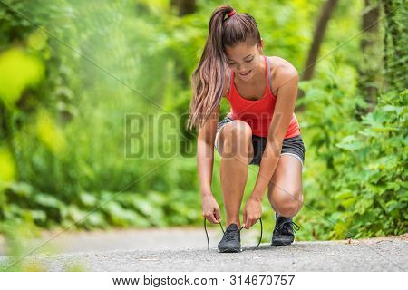 Happy woman tying running shoes getting ready to walk or run jogging in outdoor forest. Asian fit girl preparing to jog outside.