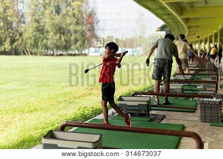 Bangkok Thailand - 27 Jul 2019 Young Asian Boy With Nike Trainer Logo Practicing His Golf Swing At S