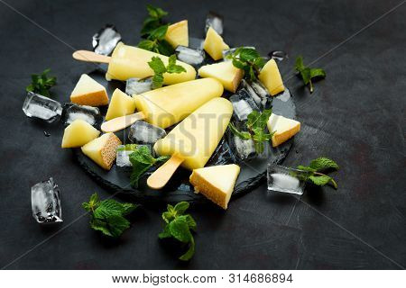 Homemade Melon Ice Cream, Pops Or Popsicles With Ice, Melon Slices And Mint On Round Dark Slate Plat