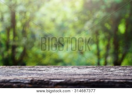 Old Wooden Table Top On Green Blurred Abstract Background From Foliage Background. Ready Used Us Dis