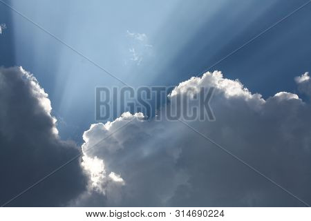 Beautiful Blue Sky With Sun Rays Coming Out Of The Clouds, Heaven. White Curly Clouds, Divine Light.