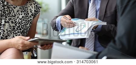 Focus On Smart Businessman Pointing At Biz Statistics. Businesspeople Sitting In Corporation Confere