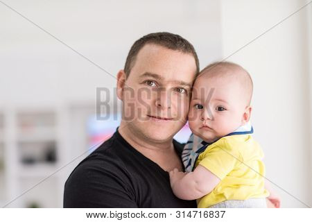 portrait of happy young father holding newborn baby boy near the window at home