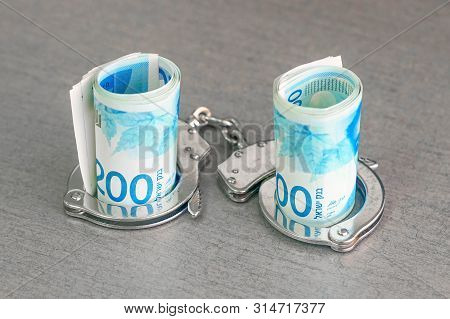 Roll Israeli Money Bills Of 200 Shekel In Handcuffs Isolated On Gray Background. Shekel Banknotes Wi