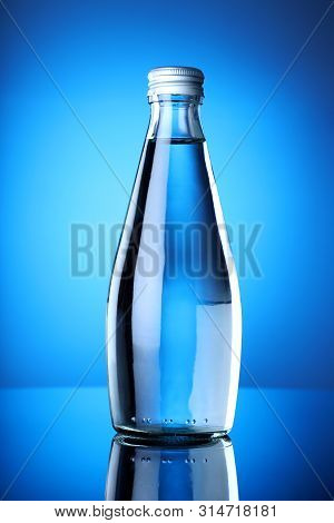Clean And Pure Mineral Drinking Water Bottle With Blue Background