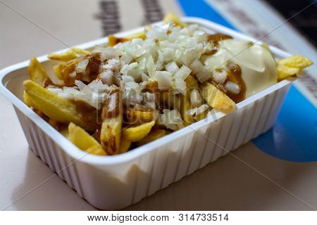 Eating Of Belgian Fried Potatos Chips With Onion, Sate And Mayonnaise, Street Fast Food, Unhealthy F