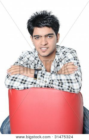 An Indian Teenager sitting on a couch.