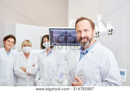 Competent dentist as a senior physician with his team of doctors in X-ray diagnostics of the dental clinic