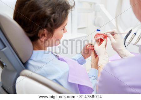 Dentist or dental assistant explains the effect of the braces or braces on the model