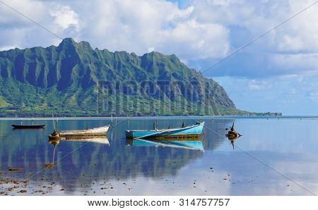 A Perfectly Still Kaneohe Bay Creates A Perfect Reflection On The Mountains And Old Boats