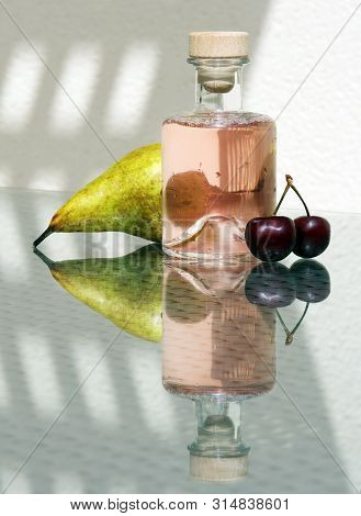 Still Life With Fresh Compote In Vintage Glass Bottle, Sweet Cherries And Ripe Pear Against A High K