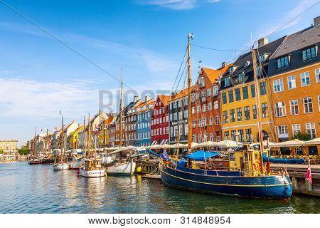Copenhagen, Denmark - July, 2019: Copenhagen Iconic View. Famous Old Nyhavn Port With Colorful Medie
