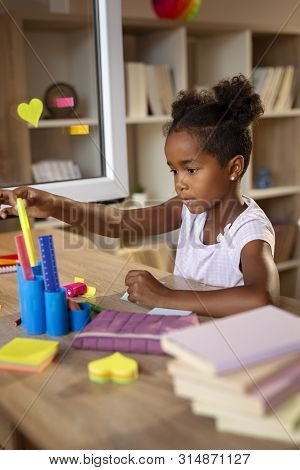 Beautiful Little Girl Sitting At Her Desk, Doing Homework And Preparing For A New Shool Day