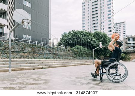 Handicapped Man In Wheelchair Playing Basketball Alone, Concept Of Adaptive Sports And Physical Acti