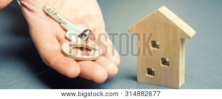 A Man Holds A Trinket Key With A House And A Wooden Home. Real Estate Concept. Realtor Services. Sal
