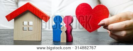 A Woman Holds In Her Hands A Red Heart Near A Miniature Family And Home. The Concept Of Property Ins