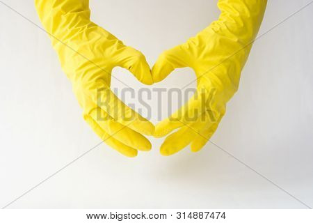 Womans Hands In Yellow Rubber Gloves In A Shape Of Heart On White Background.