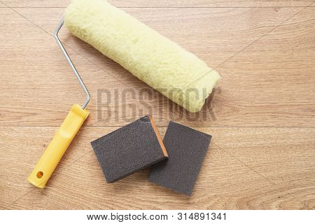 Building tools for painting surfaces. Painting roller and sandpaper on wooden background. poster