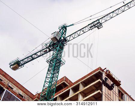 Construction Crane Near The Building Under Construction. Construction Site. Industrial Background.