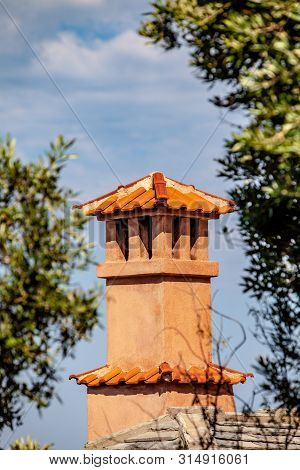 Orange Chimney On The Roof Covered With Orange Tiles Against A Background Of Pines And Blue Sky On A