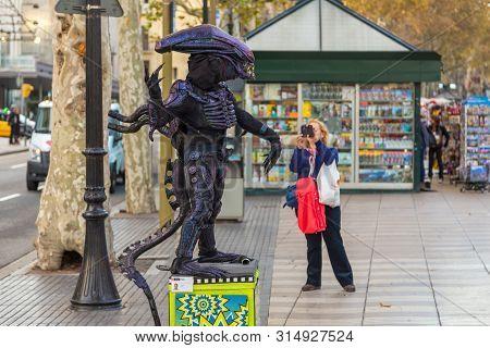 Barcelona, Spain- 10 November 2014: Living Statue Of An Alien On La Rambla Street. Woman Taking A Pi