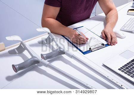 Disabled Male Patient Filling Insurance Claim Form Over Desk With Crutches
