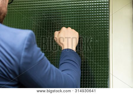 Man Standing At The Entrance Of The House Knocking The Door