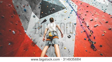 Sportsman Climber Is Looking On Steep Rock, Climbing On Artificial Wall Indoors. Extreme Sports And
