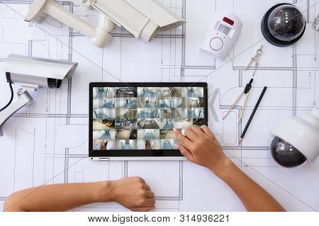 Close-up Of A Person Watching Footage On Laptop  With Security Equipment On Blueprint