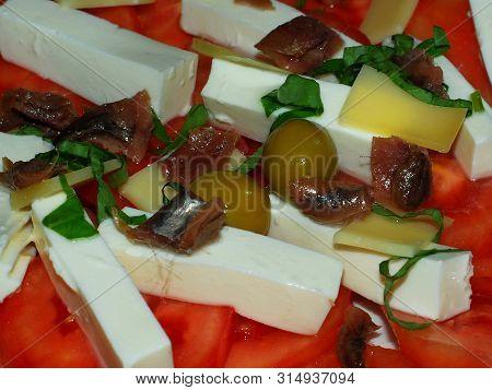 Mediterranean Food; Tomato Salad, Cheese, Anchovies, Olives And Basil