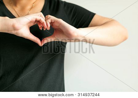 poster of Woman in black t-shirt show hand signs heart shape; by splice fingertips together; left thumb with right thumb and left forefinger with right forefinger; place at left chest. Concept of telling love.