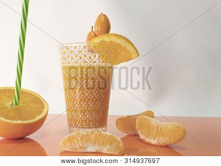 One Half Orange, Small Oranges, Orange Juice And Sliced Oranges On An Orange Table - Nutritious And