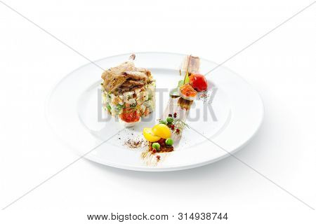 Olivier Salad or Russian Salad with Roasted Quail and Red Caviar on White Plate Isolated. Diced Potatoes, Carrots, Brined, Dill, Pickles, Green, Peas, Eggs, Onions, Mayonnaise and Spices