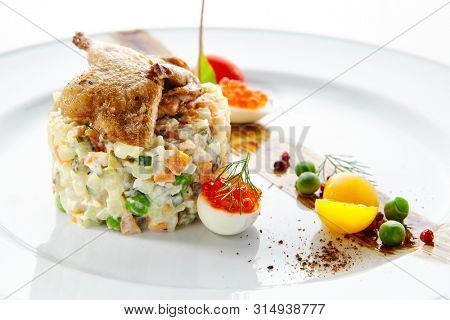 Olivier Salad or Russian Salad with Roasted Quail and Red Caviar on White Plate Isolated. Diced Potatoes, Carrots, Brined, Dill, Pickles, Green, Peas, Eggs, Onions, Mayonnaise and Spices Close Up