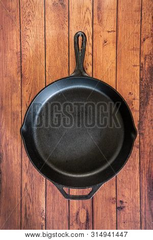 Cast Iron Skillet On Wooden Surface - Top View With Copy Space