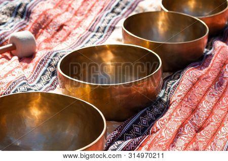 Indian Tibetan Bronze Healing Bowls Lie On A Sari In Perspective. Singing Healing Bowls Of Tibetan T