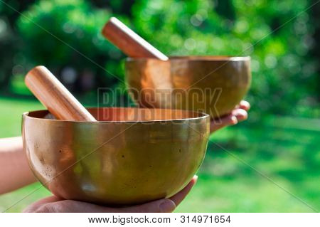 Two Singing Tibetan Bowls In Female Hands On A Background Of Green Lawn. Singing Bowls For Healing I