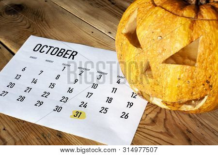Halloween Concept. October Calendar With Halloween Day Highlighted And Pumpkin - Jack-o'-lantern